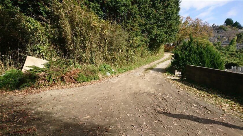 合流地点の右にはブロック塀があり、車が通れる広さがある。この霊園の横の道を行くと、高安山へ続く