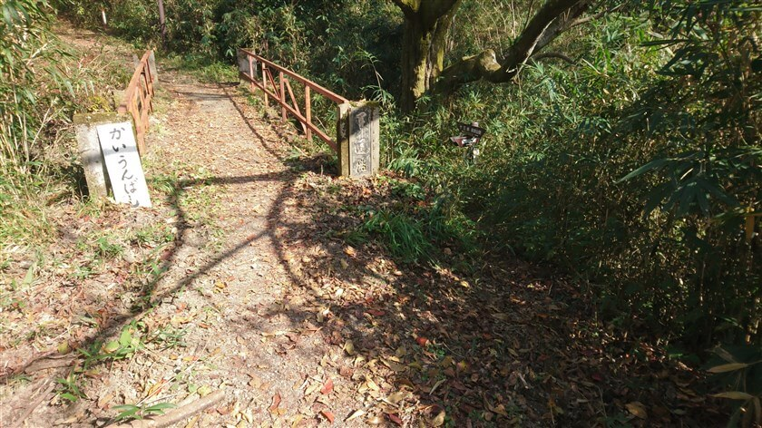 おお道越えとの合流地点の「開運橋」。右下に「左:信貴山口駅」と書かれた道標がある。