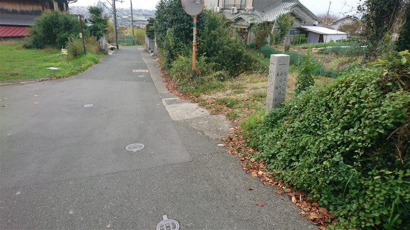 「← 佐麻多度神社」と記されている道標で、左折する