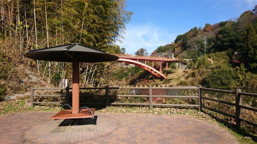 大門ダムの堰堤横に屋根付きの休憩所があり、上に信貴大橋が見える