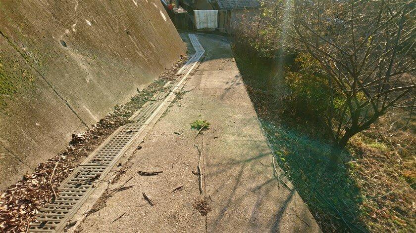 コンクリートの斜面の下に作られた道を降りる