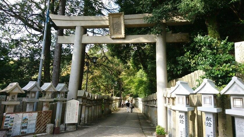 「多聞天」と掲げられた鳥居をくぐり、石灯籠の参道を行く