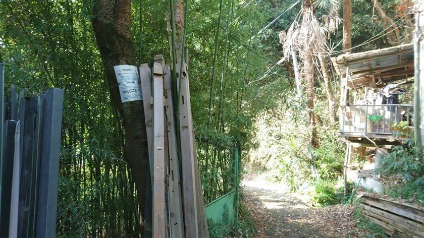 小屋があり、廃材が立てかけられた木に、通報ポイント看板「おんじごえ11」がある。(上から振り返ってしか見えない。)
