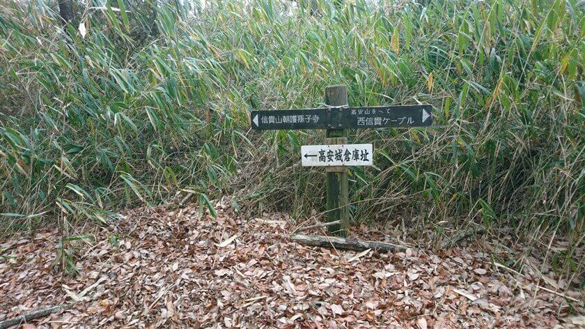「信貴山朝護孫子寺」の道標と、「← 高安城倉庫址」の案内板が掛かっている