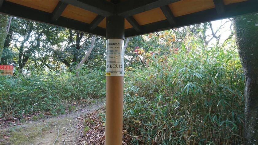 「屋根付き」休憩所の柱に、通報ポイント看板「おんじごえ12」が貼ってある