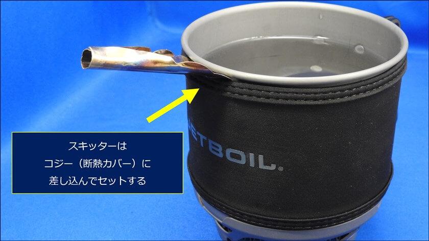 「JETBOILミニモ」には、コジーと呼ばれる断熱カバーが被せてある。これを利用して、本体との間にスキッターを挟んで固定することが出来る。