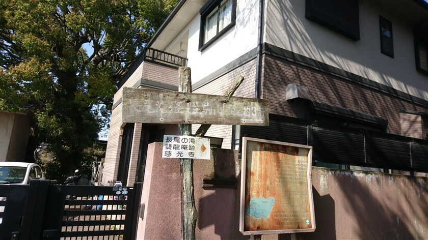住宅の角に「長尾の滝、雙龍菴跡、慈光寺 →」の標識が立っている