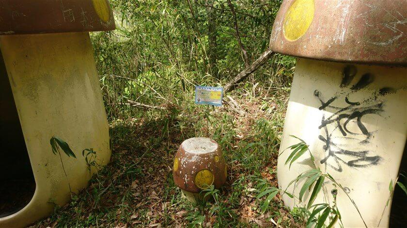 キノコ小屋の間に、「なるかわ谷コース」の位置標示標識板「な - 34」がある