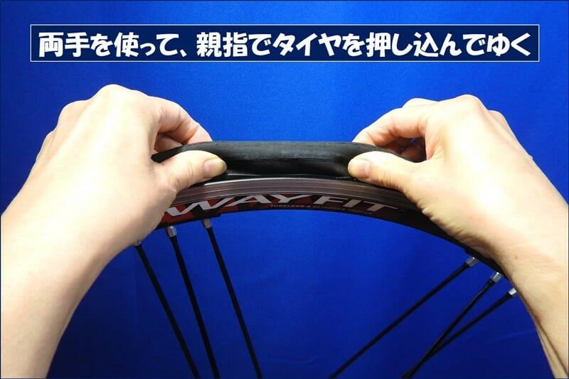 両手の親指でタイヤを押し込んでゆく