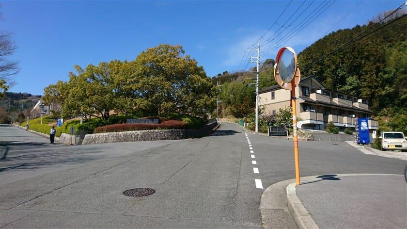 「奈良学園大学」前のバス停から、左:大学への入り口、直進:信貴山への登り。