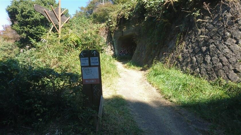 トンネルの左側には、「十三峠(0.1km)・高安山駅(4.5km)」の標識があり、歩行者用のトンネルもある
