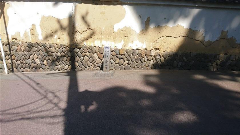 崩れ落ちそうな土塀の下に道標がある
