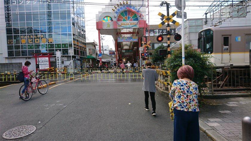 近鉄奈良線の電車が通る。右は「瓢箪山駅」で、踏切の向こうには「ジンジャモール瓢箪山」という派手な商店街が続く。