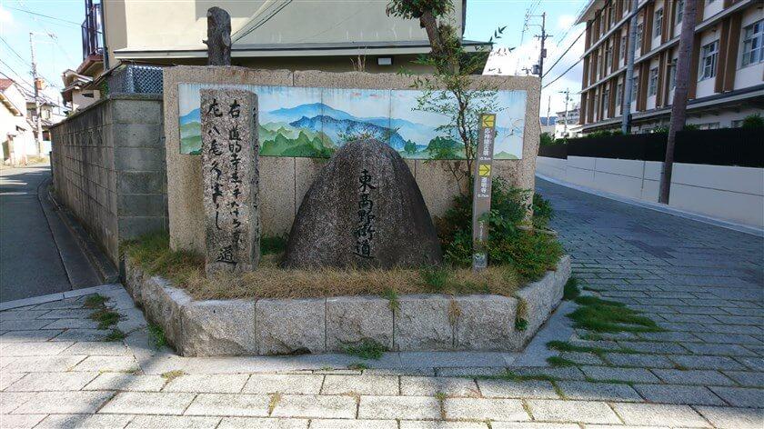 誉田中学校(右の建物)の正門前に東高野街道と八尾道の分岐点があり、天保9年(1838)の道標が置かれてる。左の道標には『右 道明寺玉手 左 八尾久宝寺』。その右に「東高野街道」の石碑がある。