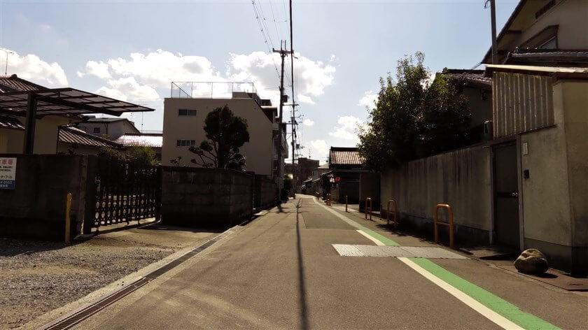 富田林市錦織中1丁目の住宅街を行く。左前のビル手前にある電柱下に石碑があるが、ロードバイクで走っていると気づくのが難しい。