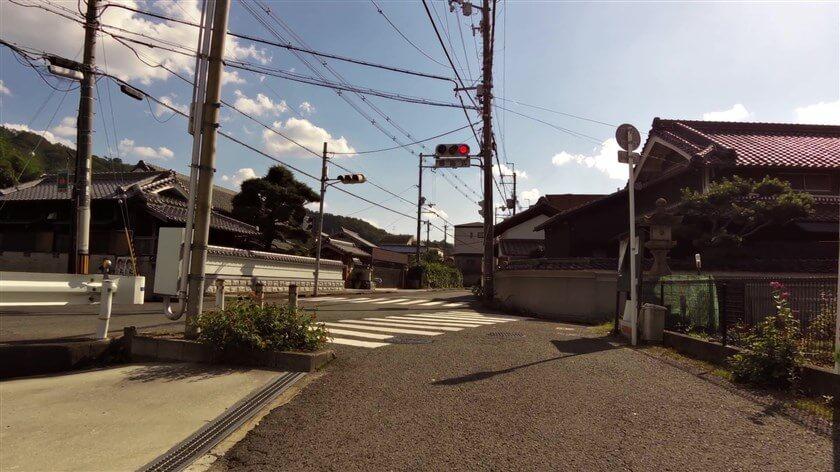 大阪府道20号と旧170号線の重複区間に出る。右の道路標識の奥に、明和の伊勢燈籠が立っている。
